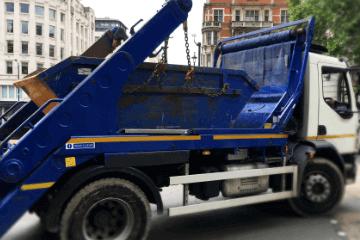 blue skip lorry delivering a skip