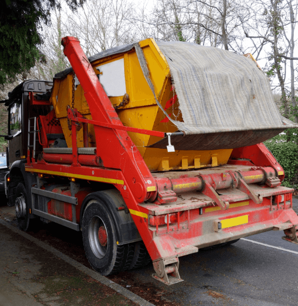 red skip lorry with a skip full of rubbish