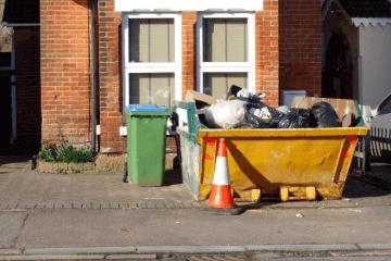 skip of waste outside a house