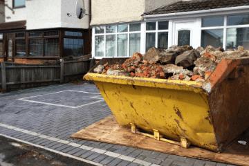 skip with rubble outside a house